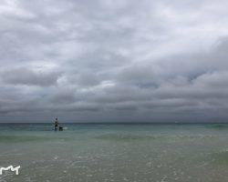 著名的白沙滩海边,海上的人站在一块板上划行,你可以叫他过来载你游玩,不过要付钱的
